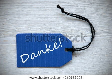 Blue Label Or Tag With Black Ribbon On White Wooden Background With German Text Danke Which Means Thank You Vintage Retro Or Rustic Style - stock photo