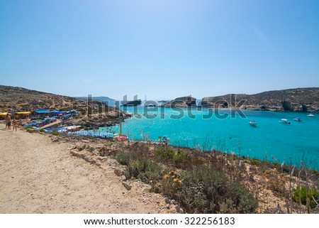 BLUE LAGOON, COMINO, MALTA - SEPTEMBER 16, 2015: Tour boats in the clear turquoise water and arid landscape of Blue Lagoon on a sunny day in September 16, 2015 in Comino island, Malta.