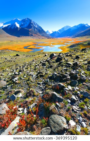 Blue lake at the foot mountain peaks. The stones and the wilderness in the mountains of Mongolia. - stock photo