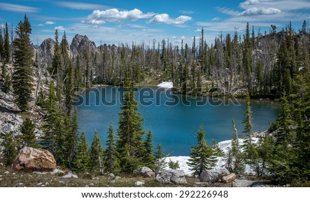 Blue lake in Idaho Sawtooth Wilderness surrounded by trees with blue sky and white clouds above. - stock photo