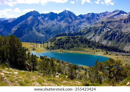 Blue lake on the pyrenée mountains from the top of a summit with a view above the lush green valley with a mountain range in the background. - stock photo