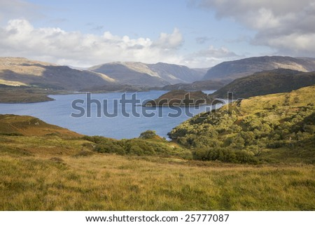 Blue lake surrounded by hills with green grassy hills in the foreground and highland hills in the background against partly cloudy sky, Scotland