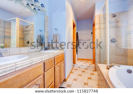 Blue large bathroom with tub and shower and wood cabinets. - stock photo