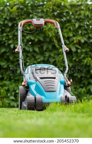 blue lawn mower in bright green grass