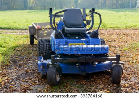 blue lawn mower in the middle of a meadow - stock photo