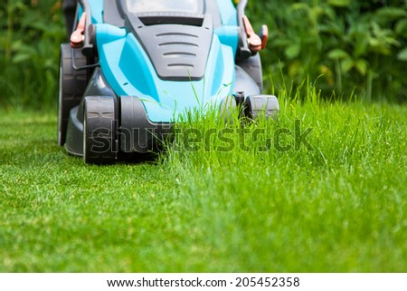 blue lawn mower on green juicy grass - stock photo