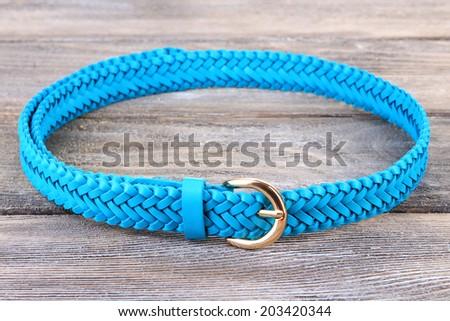 Blue leather belt on wooden background - stock photo