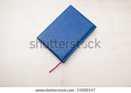 Blue leather diary book laying on wooden table - stock photo