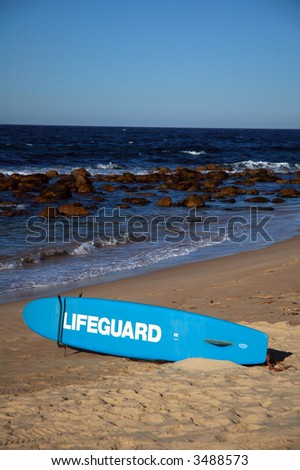 blue lifeguard surf on a beach, rocks in water, waves - stock photo