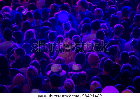 blue lighted crowd waiting for the start of the concert