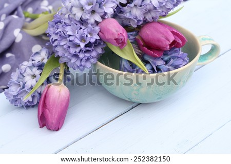 Blue, lilac hyacinth and dusky pink tulips in a green ceramic cup  bowl on wooden pale duck egg blue painted wooden boards , pretty spring image , shallow depth of field , mothers day  - stock photo