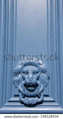 Blue lion shaped door knocker. - stock photo