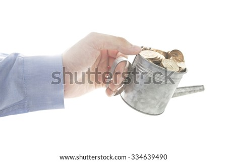 Blue long sleeve shirt Thai male hand using watering pot fully loaded with dollar coins. A concept of using money to gain more money by constantly invest some money periodically. - stock photo