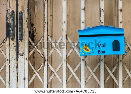 Blue Mail Box in Front of Old Rustic Metal Sliding Door, with Rust.