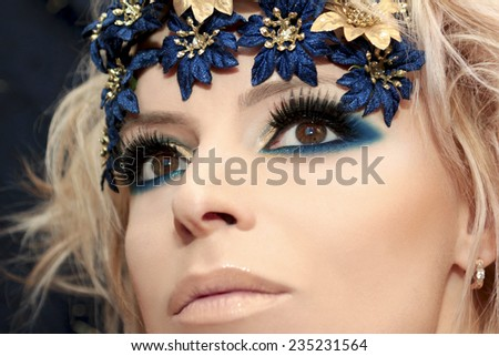 Blue makeup with decorative multicolored flowers on the blonde girl. - stock photo
