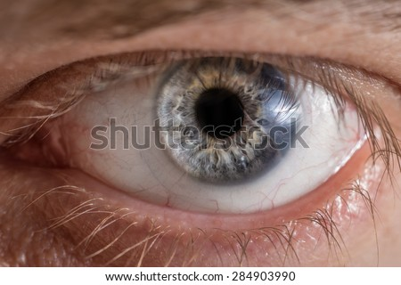 Blue man eye with contact lens, macro shot. Shallow depth of field.