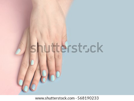 Blue manicure on female hand.