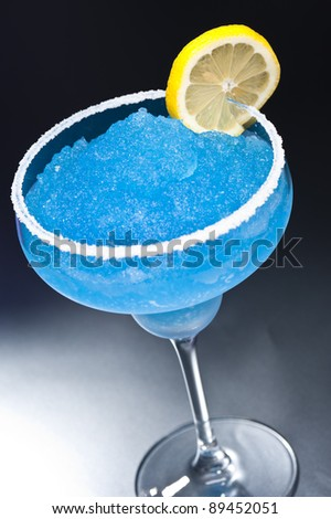 Blue margarita Cocktail in front of different colored backgrounds - stock photo