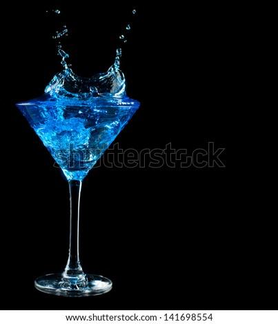 blue martini cocktail splashing into glass on black background - stock photo