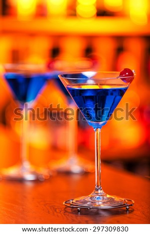 Blue martini cocktails shot on a bar counter in a nightclub