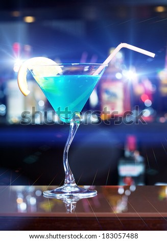 Blue Martini with Cheery in  glass over bar background on reflection surface. Shallow DOFF, nice blurred background and mixed light discos. - stock photo