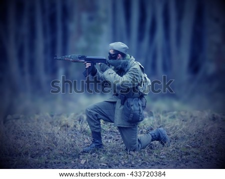 Blue Masked airsoft player, who plays for Russian side of the army, old time scenery, blurred blackground, dark vigneting - stock photo