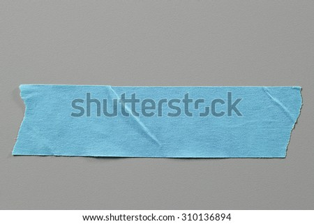 Blue Masking Tape on Grey Background with Real Shadow. Top View of Adhesive Tape, Label or Paper Tag. Sticker Close Up with Copy Space for Text or Image - stock photo