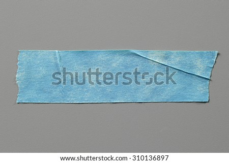 Blue Masking Tape on Grey Background with Real Shadow. Top View of Adhesive Tape, Label or Paper Tag. Sticker Close Up with Copy Space for Text or Image