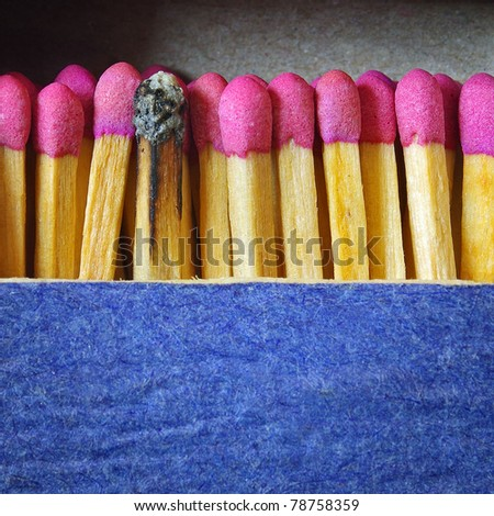 Blue matchbox with new matches and a burnt one - stock photo