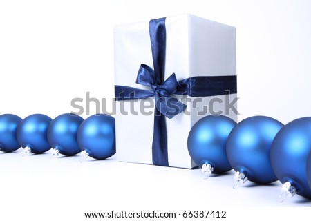 Blue matt christmas balls and a gift in silver wrapping on white background, with space for your text - stock photo