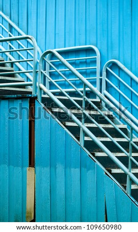 Blue metal fire exit steps beside old building. - stock photo