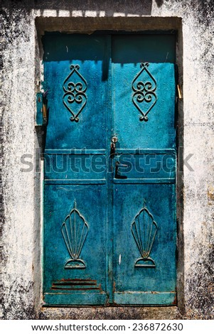 Blue metal forged door of sandstone traditional building, Middle east. Architectural theme. Photo in retro style. Paper texture. Aged textured photo in retro style  - stock photo