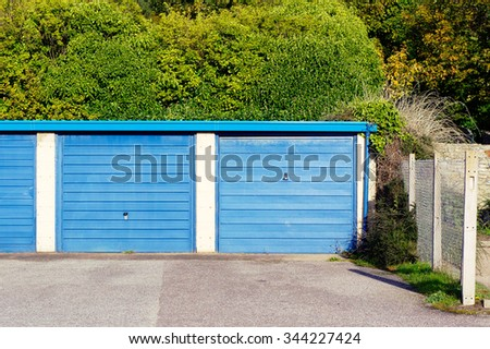 Blue metal garage doors in a car park - stock photo