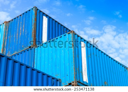 Blue metal Industrial cargo containers are stacked in the storage area under blue cloudy sky - stock photo