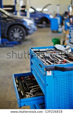 Blue metal tool cabinet with open case at service station, shallow dof - stock photo