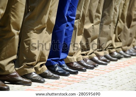 Blue military uniform stands out from a row of soldiers during military parade - stock photo