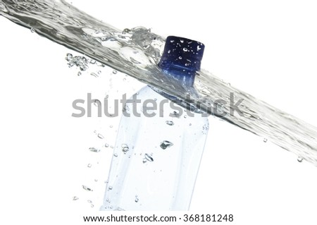 Blue mineral water bottle in pure water with waves and bubbles. Isolated on white background.