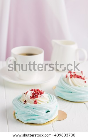 Blue mini pavlova meringue cakes with cream cheese on white background. Shallow focus - stock photo