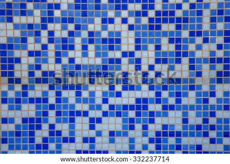 Blue modern blue background bottom of a swimming pool. Small glass tiles lined with rows of white tiles Venetian mosaic