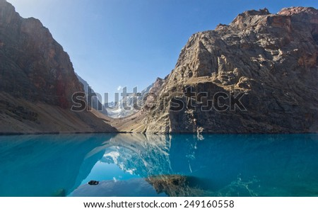 blue mountain lake surrounded by high peaks/blue mountain lake reflects high rocks - stock photo