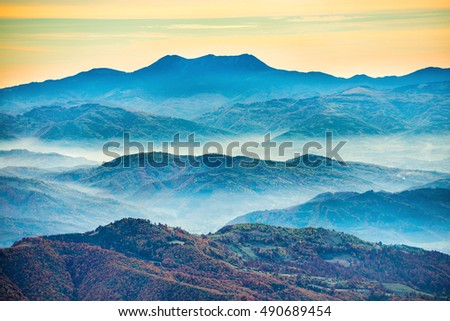 Blue mountains at sunset with white mist over hills