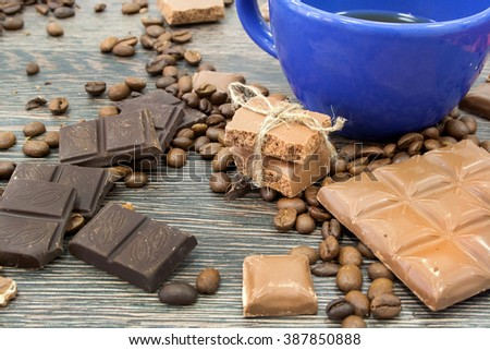 Blue Mug, a piece of chocolate bars tied with a ribbon rustic. Milk and dark chocolate. Coffee beans. The wooden surface of the table. Chocolate bar - stock photo