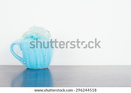 Blue mug on wooden table over grunge background. Colorful stack coffee cups on wood board. Vintage retro effect style pictures. - stock photo