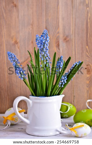 Blue Muscari flowers with Easter symbols on wooden background