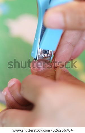 Blue Nail clipper,fingernails cut of a baby by mother.