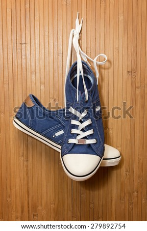 Blue, new, denim sneakers hanging on a bamboo wall - stock photo