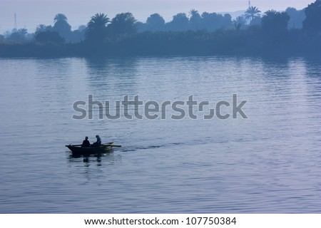 Blue Nile with fishing boat silhouette - stock photo