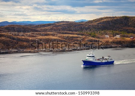 Blue Norwegian fish carrier ship in the fjord - stock photo