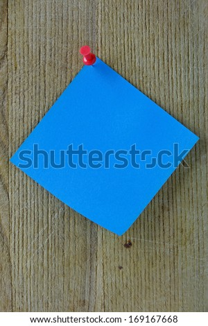 Blue note on a wooden background with red thumb-tack - stock photo