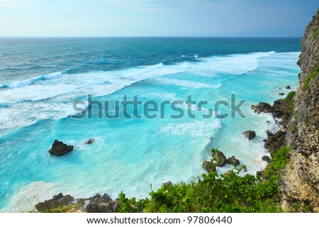 Blue ocean waves and tall cliff. Bali island - stock photo